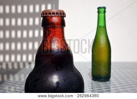 Still Life With Two Glass Bottles Of Beer With Drops Against A High Key Background With Space For Yo