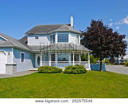 Large Residential House With Surrounding Porch And Big Green Lawn At The Entrance. Big Family Home W