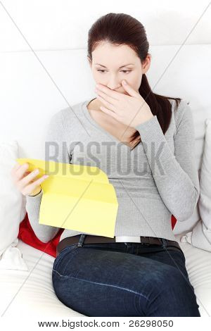 Front view portrait of a beautiful young woman having a look at the documents, being negatively surprised.