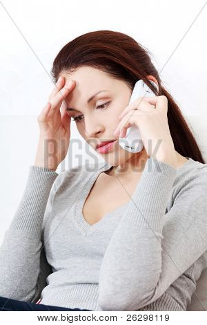 Front view portrait of a young beautiful worried woman sitting on a sofa, talking on a phone, holding her hand next to the forehead.