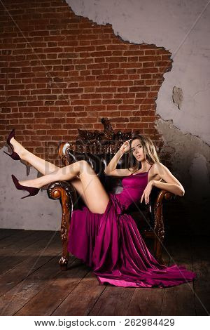 Magnificent Young Woman In Luxurious Dress A Is Sitting In A Chair Putting Your Feet On The Back In