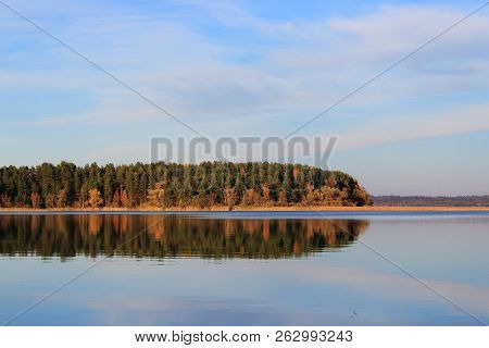 Beautiful autumn yellow forest on sunset. Sunset on the lake. Evening landscape. Clouds reflected in the water. The horizon at sunset. Sea, lake at sunset. The waves on the river. The lake in Russia