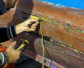 The sailor repairs his fishing boat by clogging the cracks in the timber with a cotton rope poster