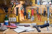 Wooden workbench at workshop. Lot of different tools for diy and repair works. Wood messy table with notebook. Copyspace. Labour day poster