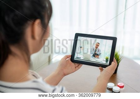 Back View Of Woman Making Video Call With Her Doctor While Staying At Home. Close Up Of Patient In V