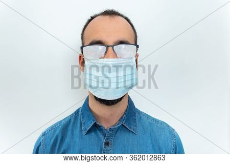 Man In Denim Shirt, Face Mask And Misted Glasses On White Background