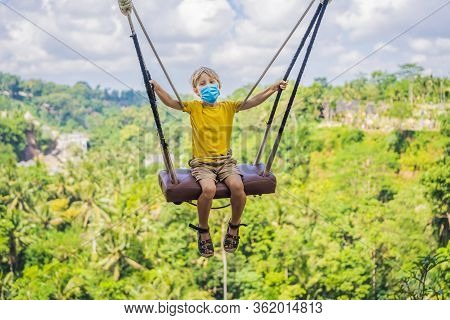 Young Boy In Medical Mask Swinging In The Jungle Rainforest Of Bali Island, Indonesia. Swing In The