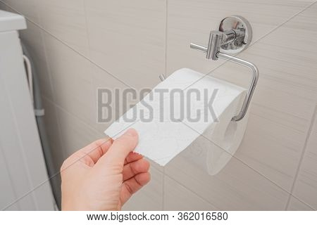Woman Sitting On A Toilet In A Restroom And Rips Off A Piece Of Toilet Paper From A Roll, Digestive