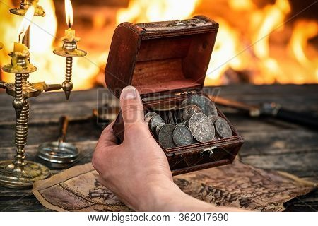 Pirate Is Looking On The Treasure Chest With Ancient Coins In His Hands Close Up On Burning Fire Bac