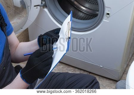 Repair Of Washing Machines. The Master Came Home And Is Repairing The Washing Machine.
