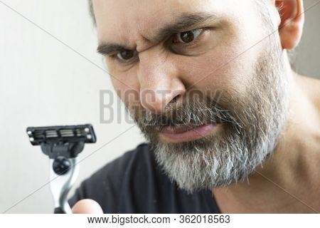 The Bearded Guy Doesnt Want To Shave. The Man Looks At The Razor With Anger, Hostility. Shallow Dept
