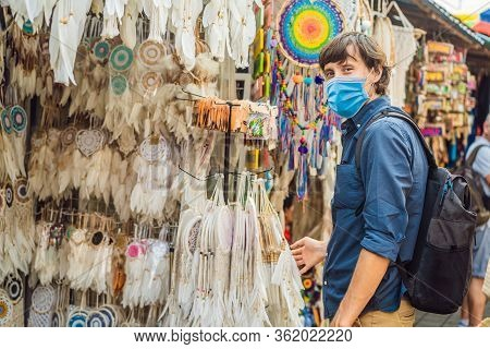 Man In Medical Mask At A Market In Ubud, Bali. Typical Souvenir Shop Selling Souvenirs And Handicraf