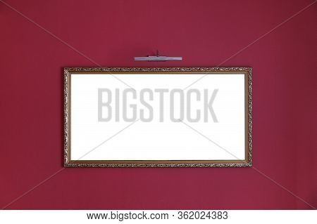 Mock Up Of Picture Frame On The Wall. Empty Picture In A Golden Baguette On A Red Wall Under A Pictu