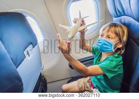 Little Boy In Medical Mask Play With Toy Plane In The Commercial Jet Airplane Flying On Vacation Tou