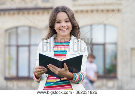 Let Your Child Discover Encyclopedia Facts. Happy Girl Hold Encyclopedia Outdoors. Reading Encyclope