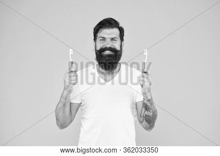 Wanted Happy Teeth. Happy Hipster Hold Brushes Yellow Background. Bearded Man Happy Smiling With Too