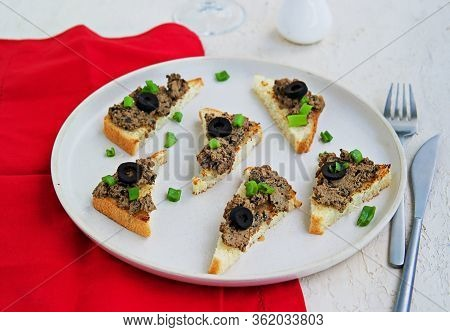Chicken Liver Appetizer With Salted Olives On Slices Of Toasted White Bread On A Light Concrete Plat