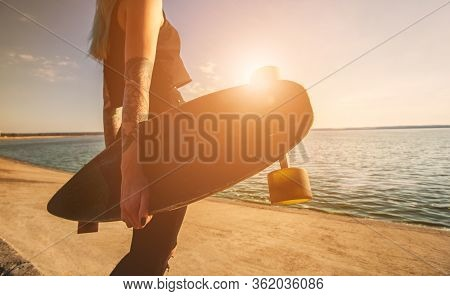 A Beautiful, Sexy Hipster Girl In Tattoo Stands With A Longboard Against The Sunset At The Sea. Long