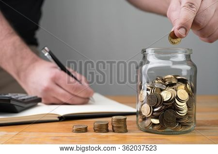 Coins In A Jar, Stacks Of Change And Young Caucasian Man Dropping Money And Writing In A Notebook. T