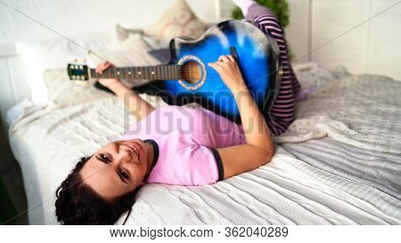 Young Woman Playing Guitar In Bedroom. Young Woman Playing The Guitar In Her Bed. She Enjoys Her Spa