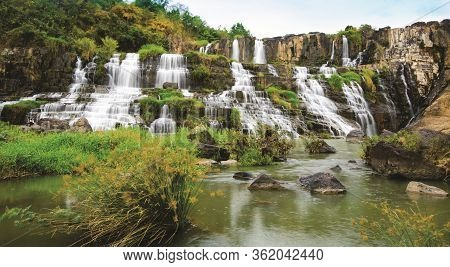 Lonely Island The Ban Gioc Waterfall With Velvety Water Flow Down River Side Fluted Foliage Foregrou