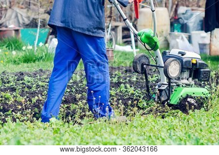 A Man Plows The Land With A Cultivator In A Spring Garden