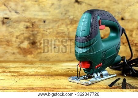 A Jigsaw Power Tool And Blades For Electric Jigsaw On Vintage Wooden Background With Copy Space For