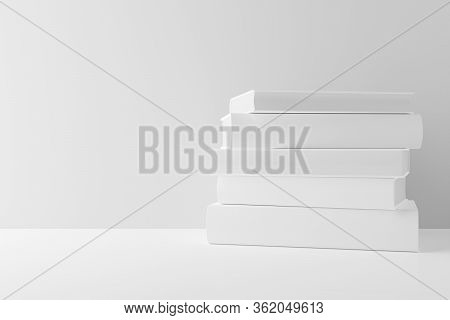 White Hardcover Books With Blank Covers Stacked On White Table Or Shelf Against White Wall Backgroun
