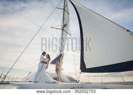 Beautiful Wedding Couple Bride And Groom On Yacht At Wedding Day Outdoors In The Sea. Happy Marriage