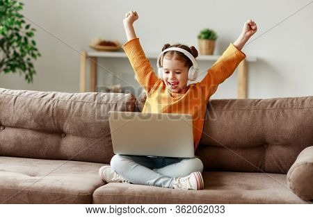 Happy Girl In Headphones Raising Arms And Smiling While Sitting Crossed Legged On Sofa And Celebrati