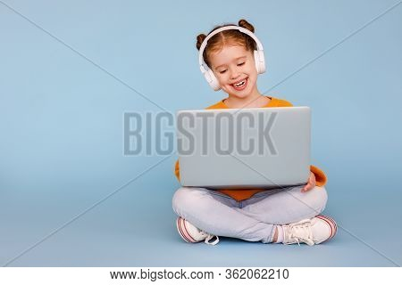 Full Body Positive Little Girl In Headphones Smiling And Watching Cartoon On Modern Laptop While Sit