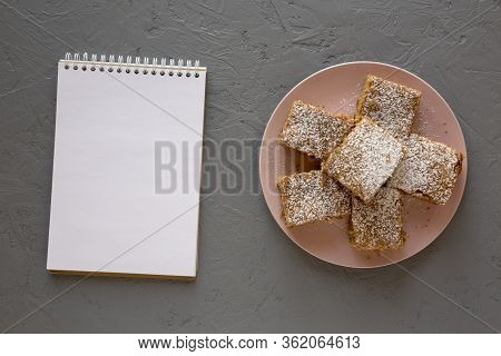 Homemade Tasty Applesauce Cake On A Pink Plate, Blank Notepad On A Gray Background, Top View. Flat L