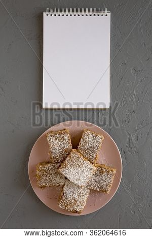 Homemade Tasty Applesauce Cake On A Pink Plate, Blank Notepad On A Gray Surface, Top View. Flat Lay,