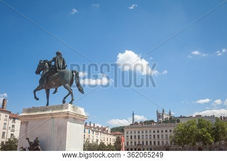 Roi Louis Xiv Statue On The Place Bellecour Square, In Downtown Lyon, With The Basilique Notre Dame