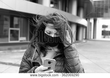 Black And White Portrait Of A Woman In A Black Medical Mask With Phone In Her Hands Reading Terrible