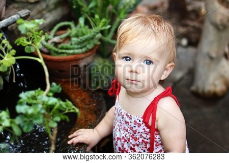 Portrait Of Little Girl With Blond Hair And Blue Eyes In Sundress In Garden With Pot Plants And Wate