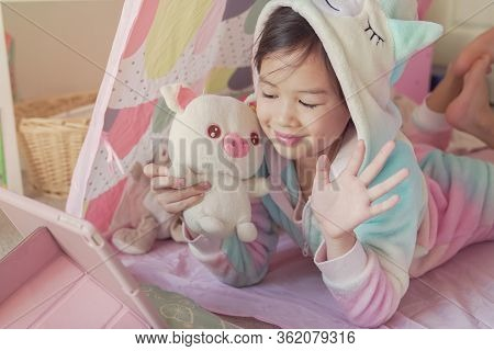Mixed Race Asian Girl Making Facetime Video Calling With Tablet At Home, Using Zoom Learning Online