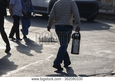Man Selling Tea In Thermos On The Street. In His Other Hand, He Carries Glass Glasses On A Handle Tr