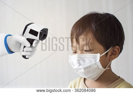Medical Infrared Thermometer In A Hand Of The Doctor Measuring The Temperature Of The Asian Little B
