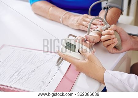 Nurse Checking Blood Pressure Of Senior Patient With Electronic Tonometer During Annual Checkup