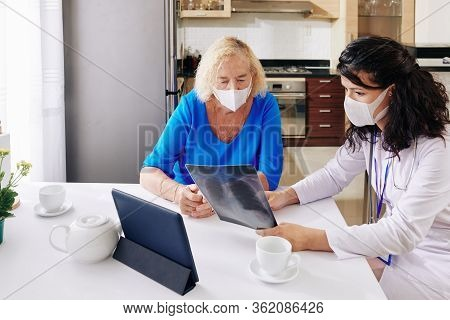 Young Female Doctor In Medical Mask Visiting Senior Patient At Home And Showing Her Lungs X-ray