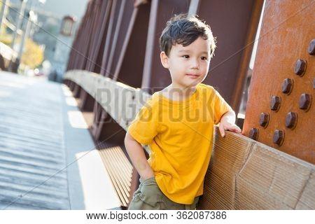 Mixed Race Chinese and Caucasian Boy Playing Alone on Bridge.