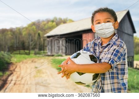 Mixed Race Hispanic and African American Boy Holding Soccer Ball Wearing Face Mask Outdoors.