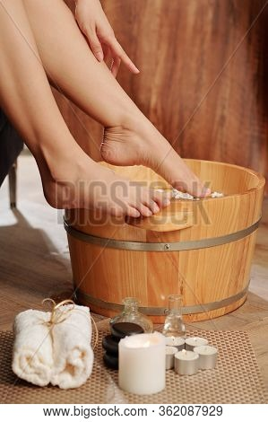 Cropped Image Of Woman Putting Feet In Basin With Hot Water To Soak It Before Doing Pedicure At Home
