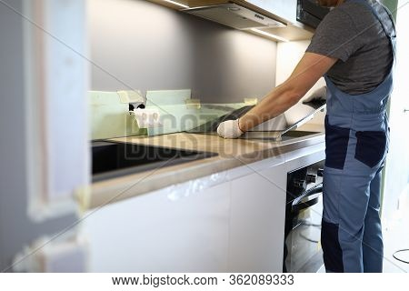Repairman Installs Hob Kitchen Table In Apartment. Installation Hob In Countertop. Purchase New Kitc
