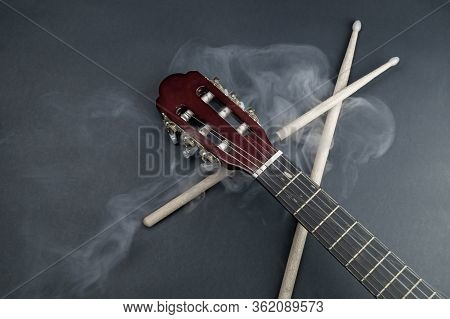 Drumsticks And Guitar Fretboard In Smoke. Acoustic Musical Instrument. Copy Space