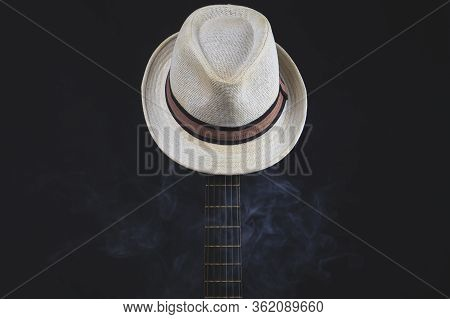 White Hat In Smoke Hangs On The Guitar Fretboard. Acoustic Musical Instrument. Strings On The Guitar