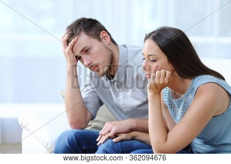 Sad Worried Couple Complaining Together Holding Hands On A Couch At Home