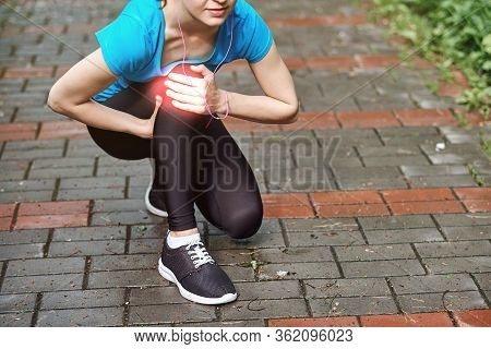 Woman Athlete Runner Touching Knee In Pain, Fitness Woman Running In Summer Park. Healthy Lifestyle