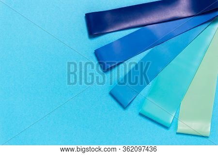 Set Of Elastic Rubber Resistance Bands In Blue, Turquoise And Green On Blue Background. Equipment Fo